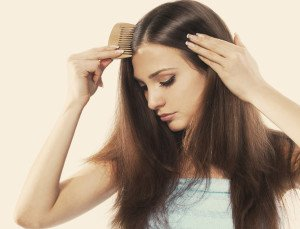 A young woman with beautiful long hair combing her locks