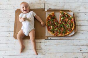 Kas mėnesį kūdikio nuotrauka šalia picos, kurios gabaliukai simbolizuoja mėnesius